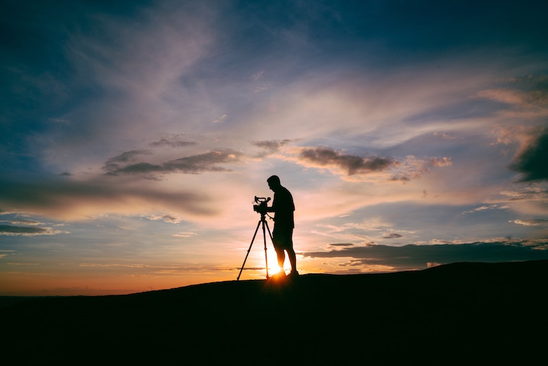 Person making a video with a cloudy, colorful sunrise in the background