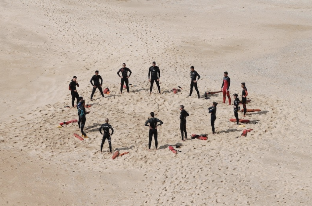 Team of scuba divers in wetsuits in a circle facing each other with gear on the sand beside them