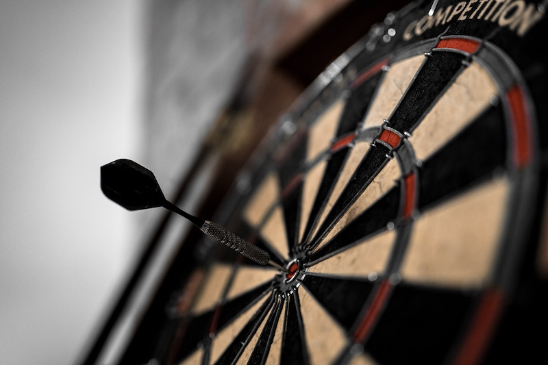 Bullsye - a black dart is right in the middle of a black, beige, and red dartboard, representative of ad targeting on Facebook